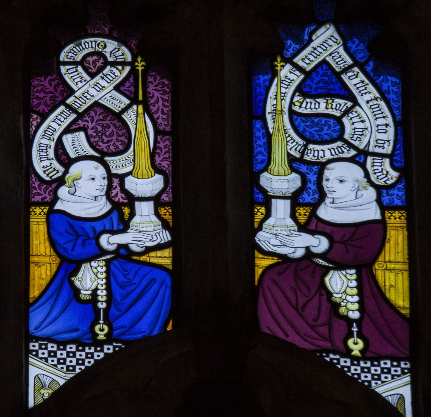 Detail of figures in the stained glass holding the font complete with covers.