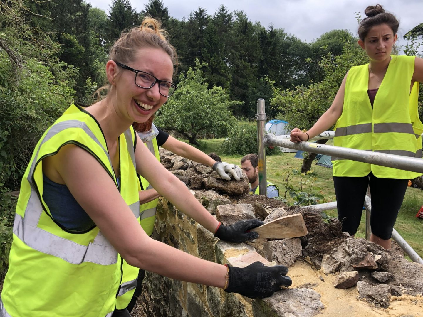 Rachel rebuilds the top of a stone wall at the SPAB working party 2019